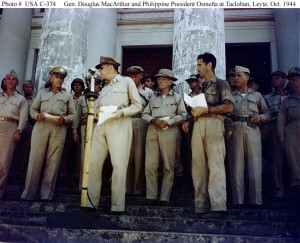 General Douglas MacArthur at the microphone during ceremonies marking the liberation of Leyte, at Tacloban, October 23, 1944. Philippine President Sergio Osmeña is in the center, one step behind MacArthur. At left are Lieutenant Generals Walter Kreuger and Richard K. Sutherland. Photograph from the Army Signal Corps Collection in the U.S. National Archives.